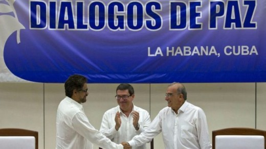 Colombian government negotiator Humberto de la Calle (R) and his Farc counterpart Ivan Marquez (L) signed the agreement, applauded by Cuban Foreign Minister Bruno Rodriguez