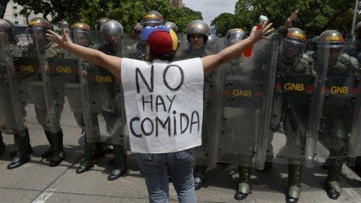 "A woman with a sign reading ""There is no food"" protests in front of a line of policemen in Caracas"