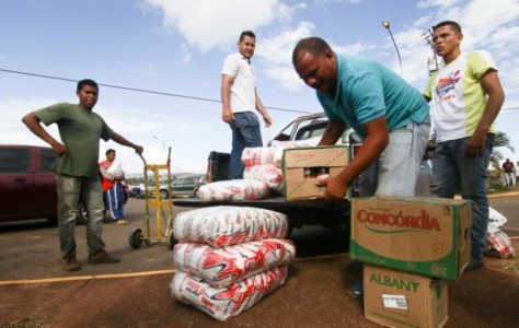 Men load boxes of food onto the back of a pick-up truck, after arriving from Brazil, in front of the bus terminal in Santa Elena de Uairen, Venezuela August 2, 2016. REUTERS/William Urdaneta