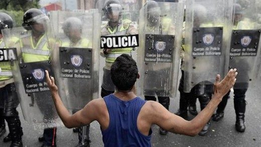 Carlos Becerra | Bloomberg | Getty Images A protester gestures in front of police during an opposition march in Caracas, Venezuela, on Wednesday, May 11, 2016.